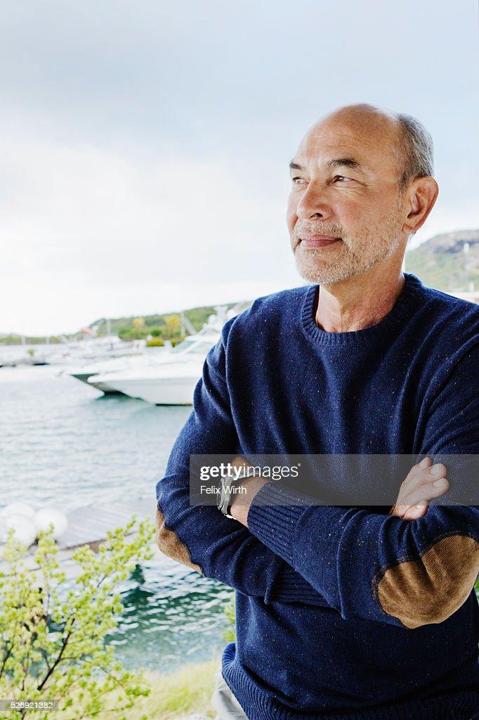 Portrait of senior man posing in front of marina : Foto de stock