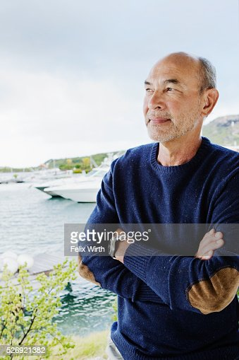 Portrait of senior man posing in front of marina : Photo