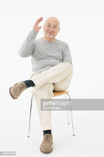 Portrait of senior man raising hand, sitting on chair with legs crossed, studio shot