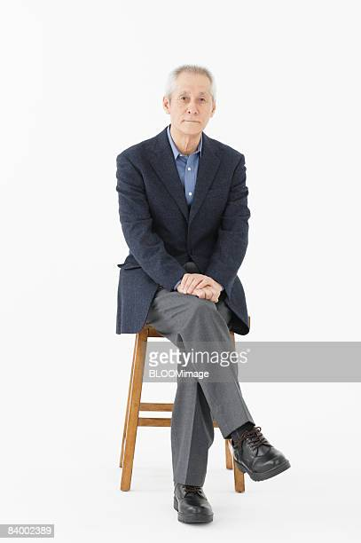 Portrait of senior man sitting on chair with legs crossed, studio shot