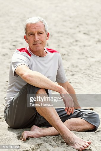 Portrait of senior man sitting on sand looking at camera : ストックフォト