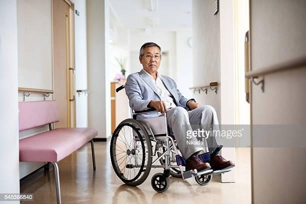 Portrait of senior man sitting on wheelchair in hospital