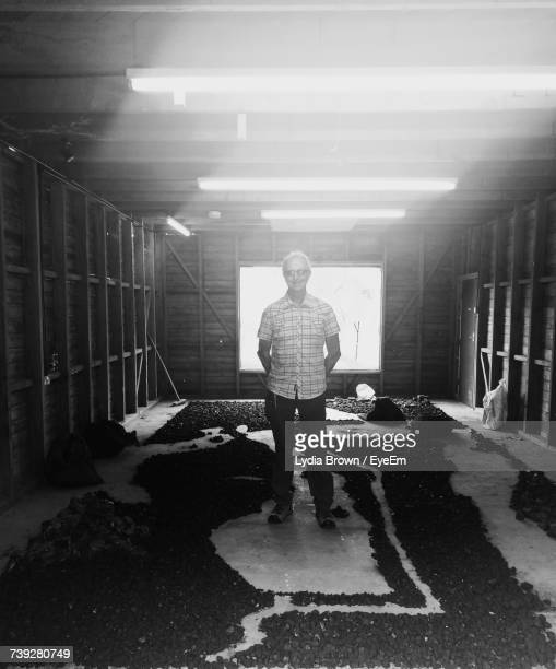 Portrait Of Senior Man Standing In Incomplete Room At Construction Site