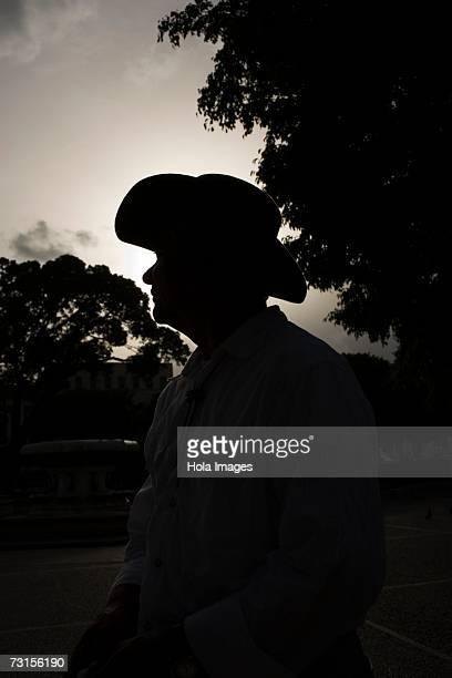 Portrait of senior man wearing hat, outdoor silhouette