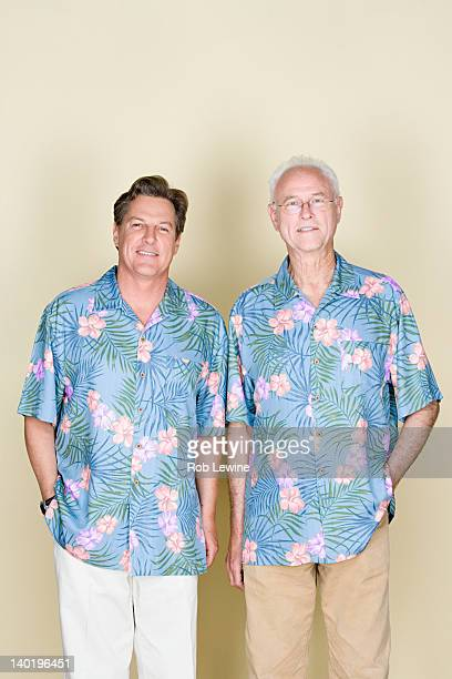 Portrait of senior man with adult son wearing Hawaiian shirts