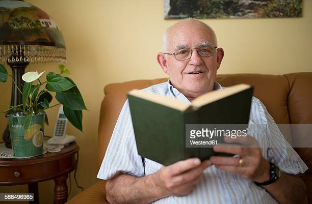 Portrait of senior man with book at home