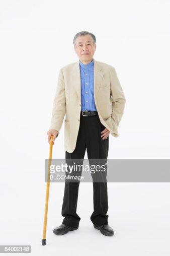 Portrait of senior man with cane, studio shot