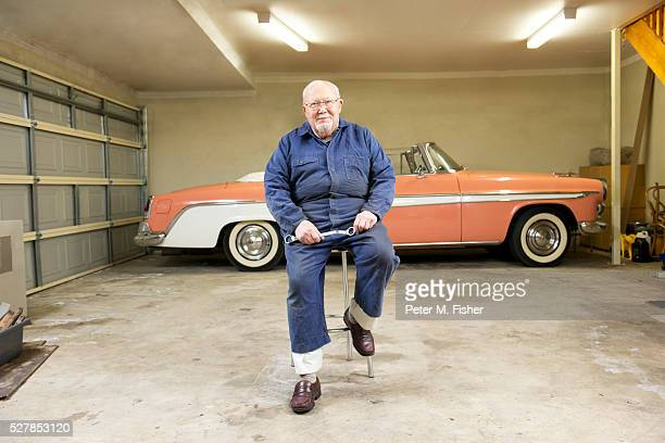 Portrait of senior man with classic vintage car in garage