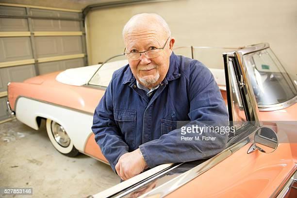 Portrait of senior man with classic vintage car in garage