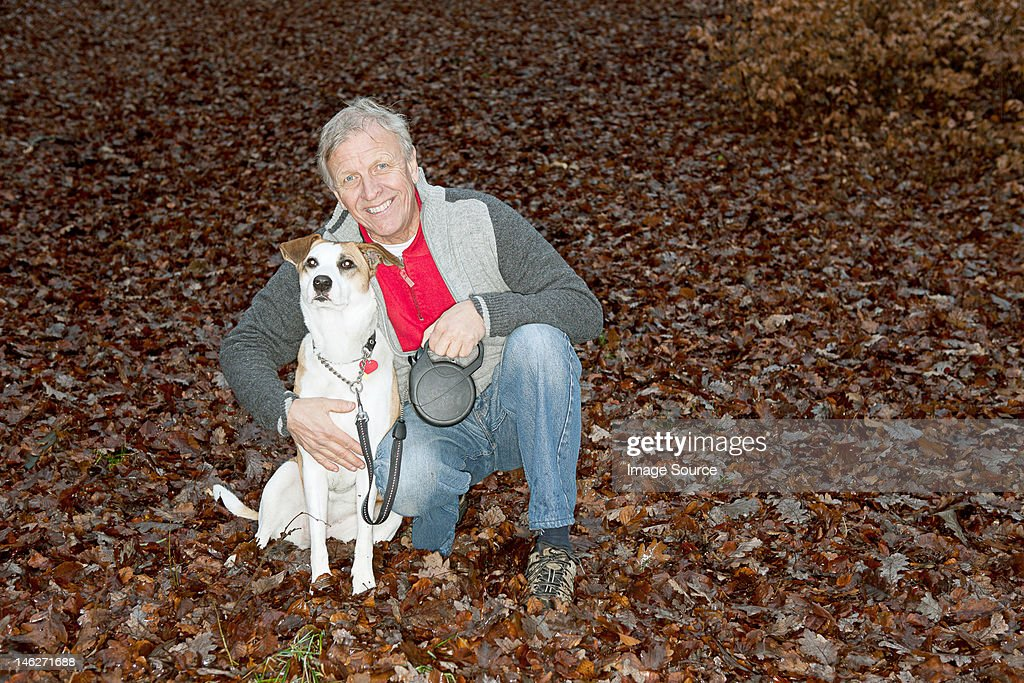 Portrait of senior man with dog in forest : Stock Photo