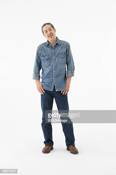 Portrait of senior man with hands on hips, studio shot
