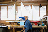 Portrait of senior man with laptop and model sailboats