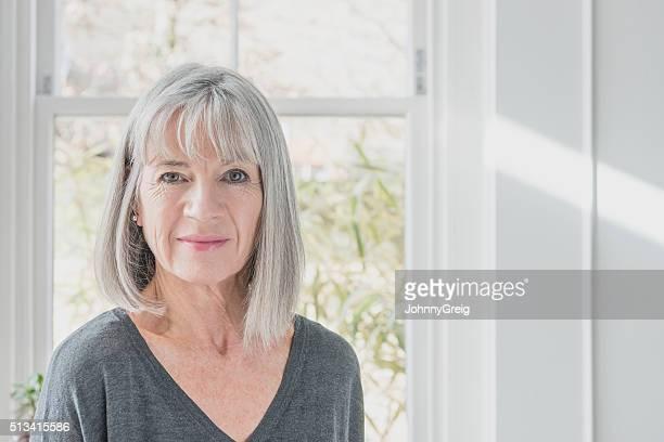 Portrait de femme âgée par la fenêtre avec Bob gris