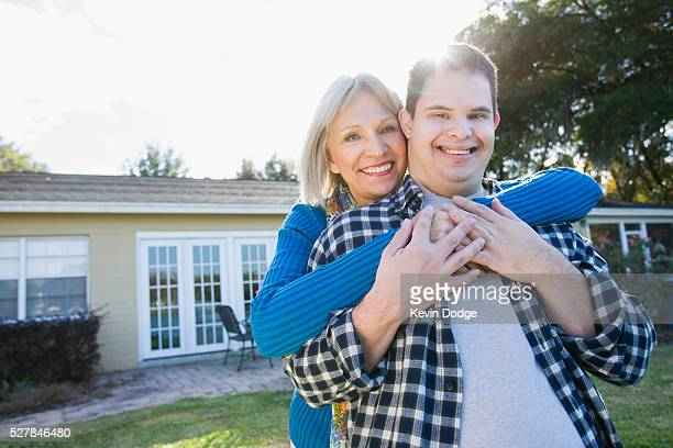 Portrait of senior woman embracing son (16-17) with Down Syndrome
