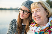 Portrait of senior woman head to head with her adult granddaughter