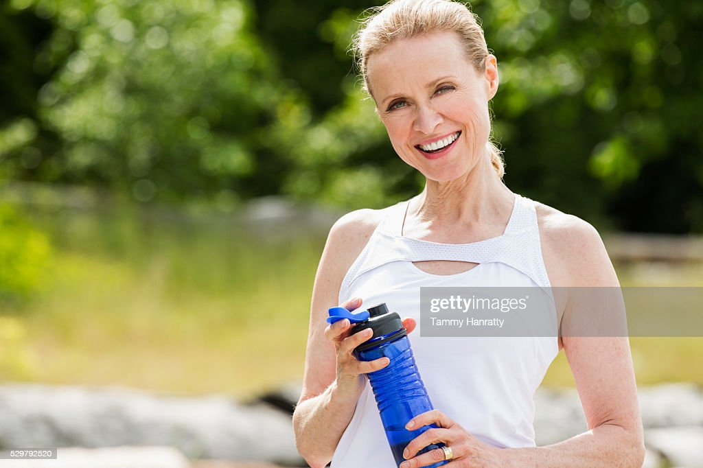 Portrait of senior woman holding bidon outdoors : Stock Photo