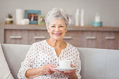 Portrait of senior woman holding coffee cup at home