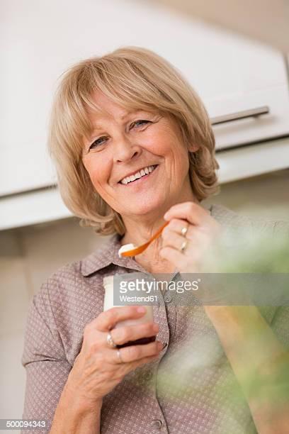 Portrait of senior woman holding glass of yogurt