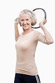 Portrait of senior woman holding tennis racket over her shoulder against white background
