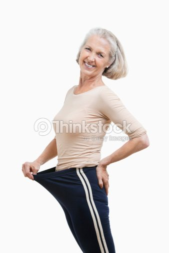 Portrait of senior woman in oversized pants against white background : Stock Photo