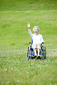 Portrait of senior woman in wheelchair waving hand in the field, smiling and looking at camera