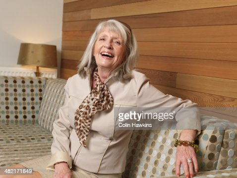 portrait of senior woman laughing on sofa photo getty images. Black Bedroom Furniture Sets. Home Design Ideas