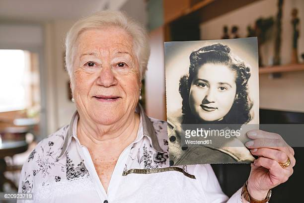 Portrait of senior woman showing an old picture of herself