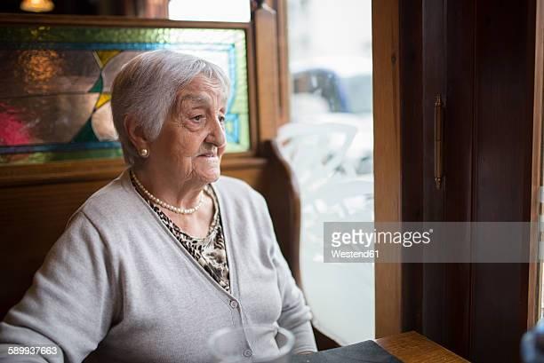 Portrait of senior woman sitting in a restaurant looking through window