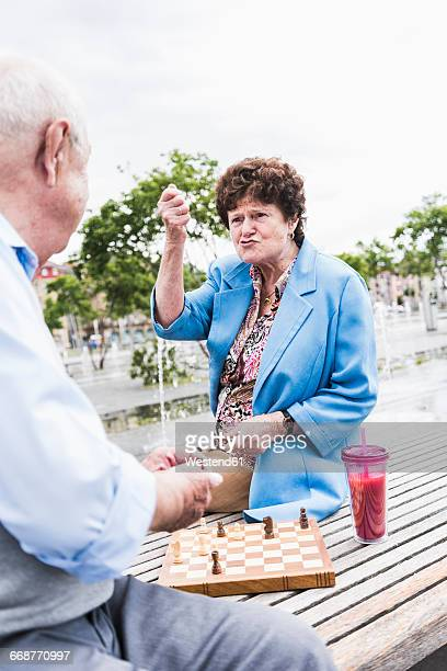 Portrait of senior woman sitting on a bench playing chess with her husband