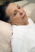 Portrait of senior woman sitting up and sleeping on sofa, close-up