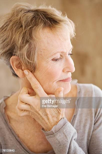 Portrait of senior woman touching her ear