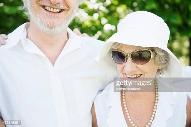 Portrait of senior woman wearing sunglasses and white sunhat