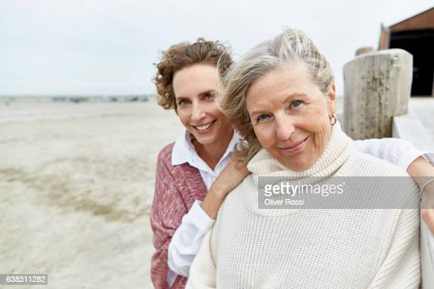 Portrait of senior woman with adult daughter on the beach