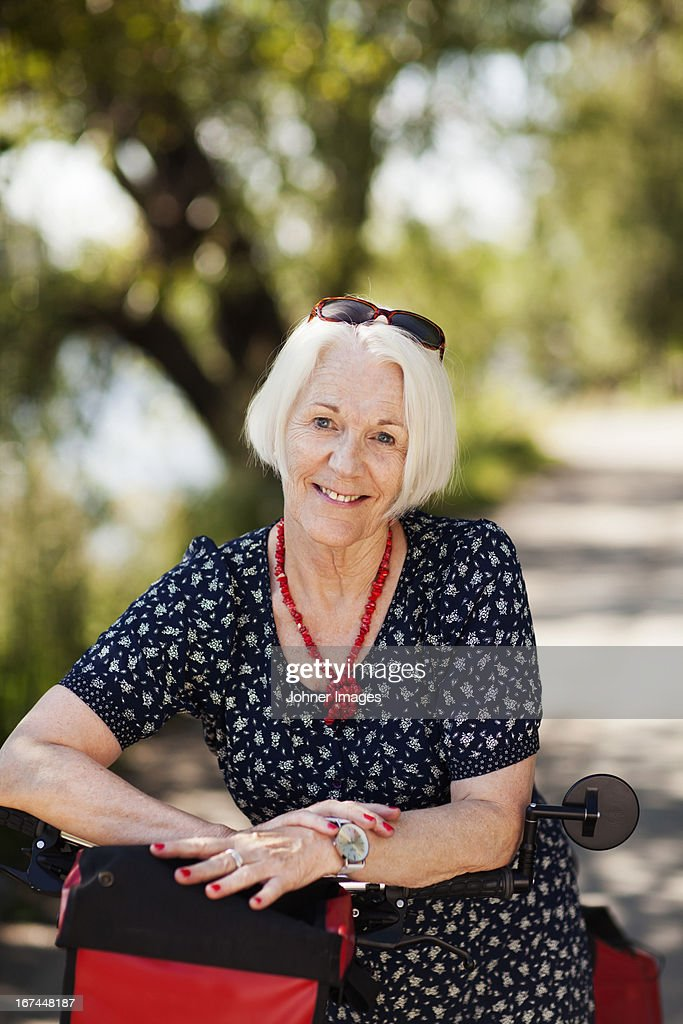 Portrait of senior woman with bicycle : Stock Photo