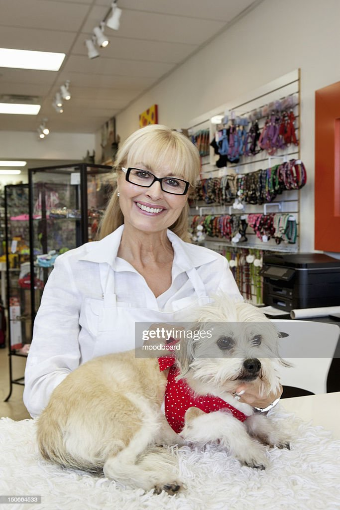 Portrait of senior woman with dog in pet shop