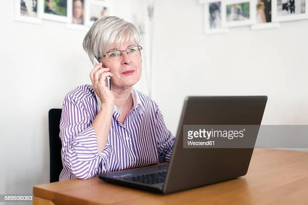 Portrait of senior woman with laptop telephoning with smartphone