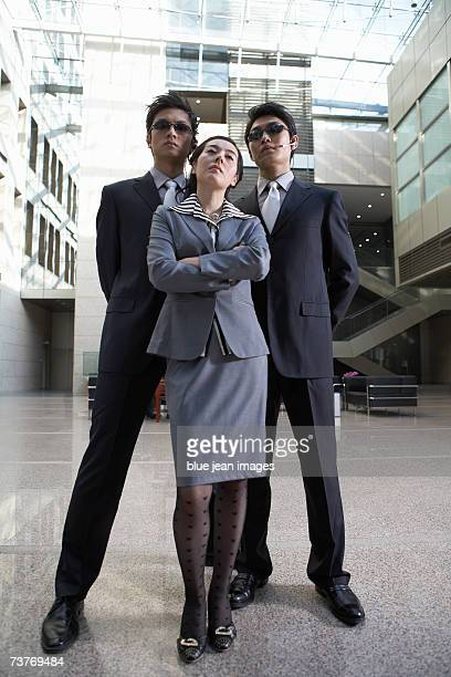 Portrait of serious businesswoman in grey standing in front of two men in dark sunglasses and headsets