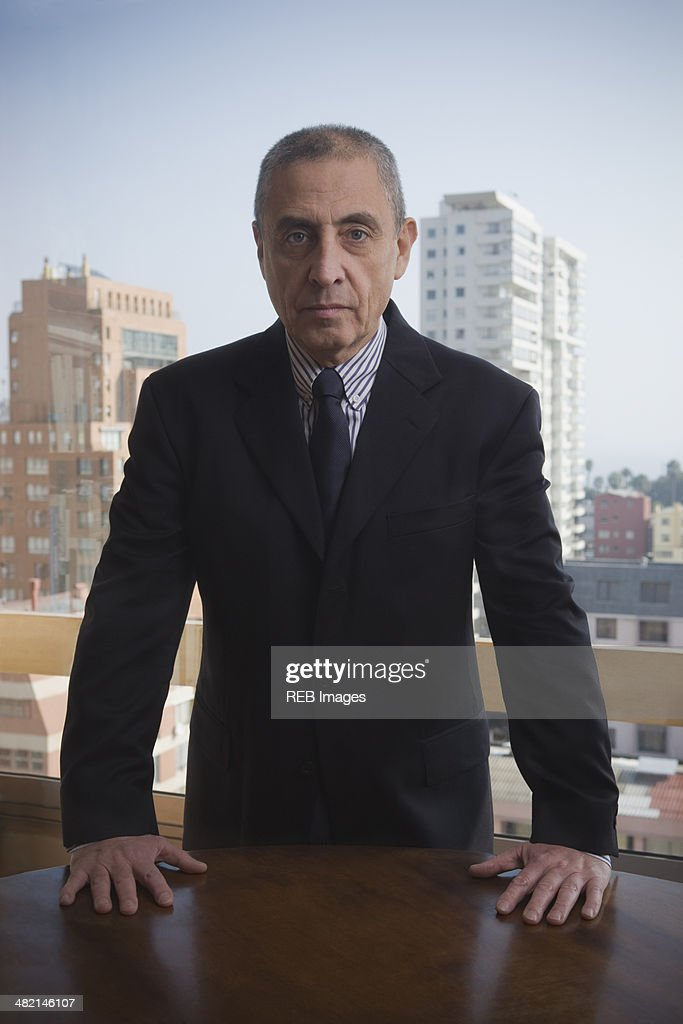 Portrait of serious Hispanic businessman in urban office