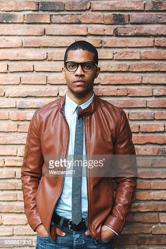 Portrait of serious looking businessman with hands in his pockets wearing leather jacket and glasses