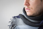 Portrait of serious man with knitted scarf isolated on gray background. Winter time accessories concept.