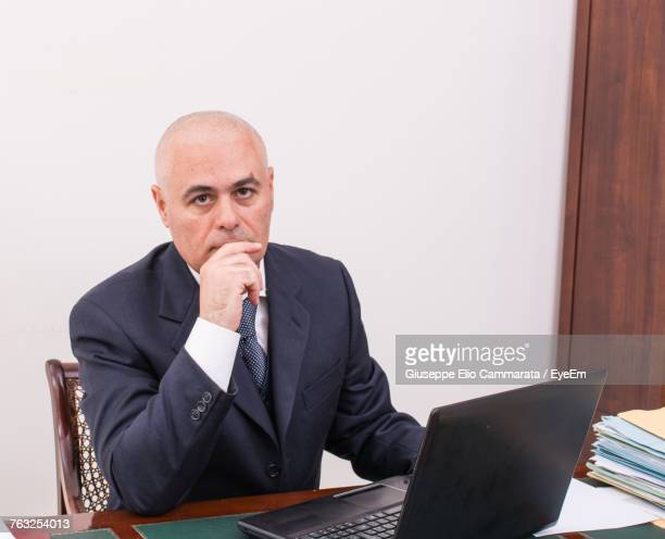 Portrait Of Serious Mature Businessman Working In Office