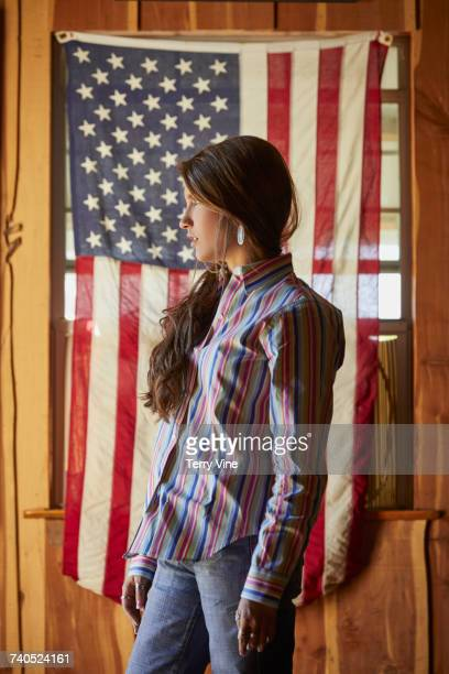 Portrait of serious Mixed Race teenage girl posing near American flag
