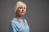 portrait of serious senior woman isolated on grey in studio