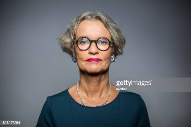 Portrait Of Serious Woman Against Gray Background