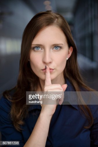Portrait of serious young businesswoman with finger on lips in office