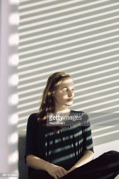 Portrait of serious young woman sitting in a shadowed room