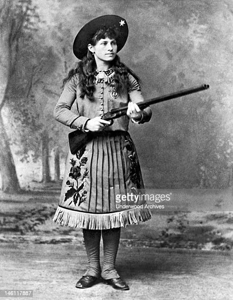 A portrait of sharpshooter Annie Oakley holding a shotgun mid 1880s