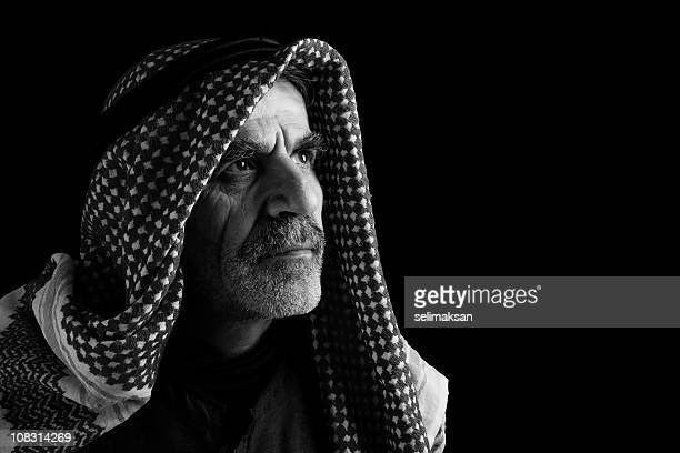 Portrait of sheik in keffiyeh and headscarf on black background