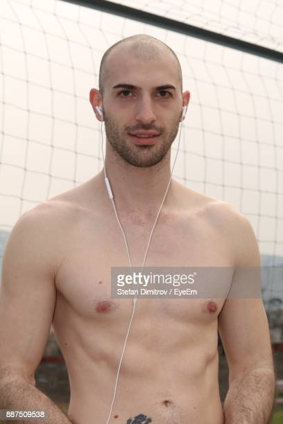 Portrait Of Shirtless Man Listening Music While Standing Against Net