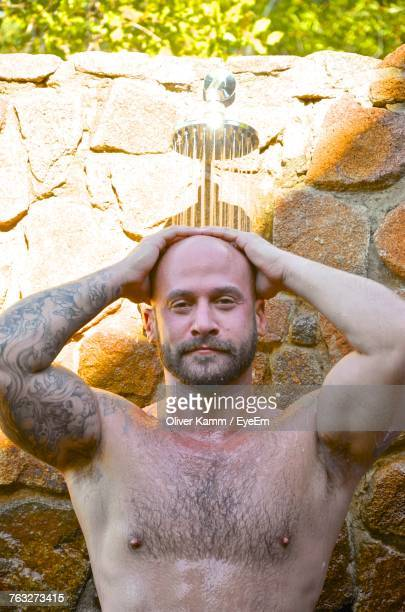Portrait Of Shirtless Man Taking Bath From Shower While Standing Against Wall